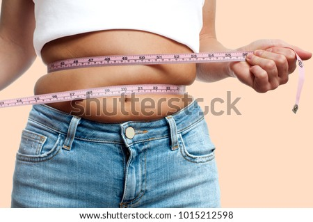 Overweight woman with tape measure around waist on pastel background