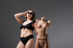 overweight young woman in black swimsuit and sunglasses posing with plastic mannequin isolated on grey