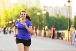 Overweight young woman jogging in the street. Weight loss concept