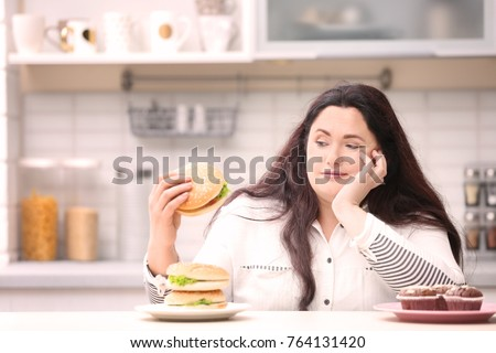 Overweight young woman with unhealthy food at table in kitchen