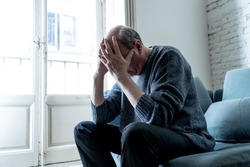 Overwhelmed old senior man suffering alone at home feeling confused sad alone on couch at home in Aging Retirement widower Dementia and Alzheimer concept.