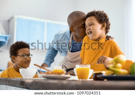 Overwhelmed with feelings. Affectionate young father kissing his little son on the cheek while he having breakfast in the kitchen #1097024351