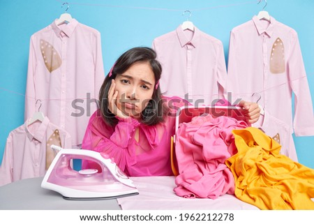 Overworked Asian woman looks sadly at camera leans at ironing board irones clothes prepares laundry for ironing poses against blue wall with ironed shirts on hangers. Domestic everyday duty.