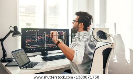 Overworked. Back view of tired young beard businessman or trader in formal wear touching his head and stretching while sitting in office.