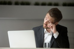 Overworked businessman in suit tired from laptop work, exhausted man feeling lack of sleep, headache or eye strain at workplace, office worker suffering from chronic fatigue after long using computer