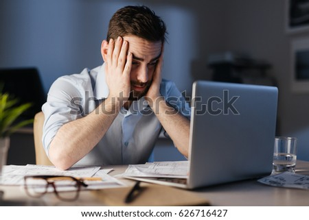 Overworked businessman sitting in front of laptop