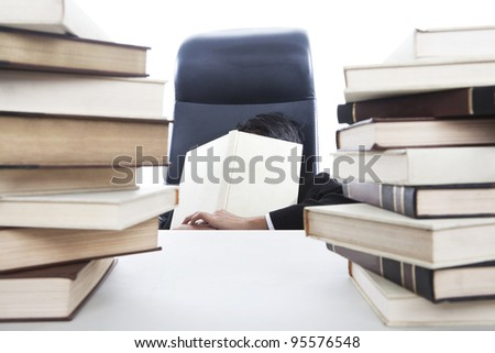 Overworked businessman sleeping in office while holding a book - stock photo