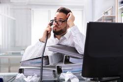 Overworked Businessman Talking On Landline With Stack Of Folders On Desk