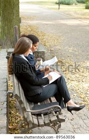 overworked businesswomen working on bench in park