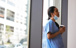 Overworked Nurse In Scrubs With Face Mask Takes Coffee Break In Busy Hospital During Health Pandemic