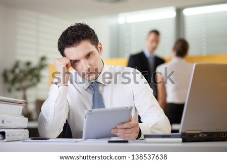 Overworked tired businessman sitting at his desk in the office using tablet computer