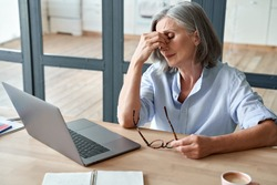 Overworked tired older lady holding glasses feeling headache, having eyesight problem after computer work. Stressed mature senior business woman suffering from fatigue rubbing dry eyes at workplace.