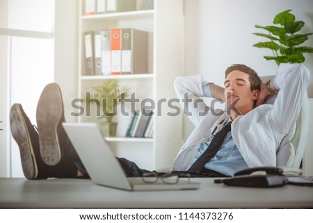 Overworked, tired young businessman sleeping at his desk in office, in front of computer. #1144373276