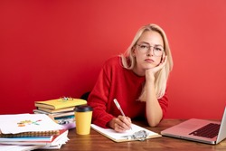 overworked unhappy and frustrated young caucasian woman in stress sitting at office desk, she has a lot of tasks in work, deadline, isolated red background