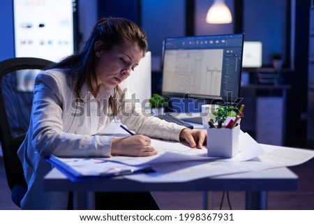 Overworked woman architect checking and matching blueprints sitting at office desk in front of computer. Perfectionist designer using arhitecture blueprints of buildings creating industrial prototype Imagine de stoc ©