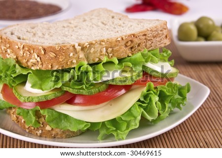 Ovo-lacto vegetarian sandwich, containing: cheese, lettuce, tomato, egg and zucchini in a wholegrain bread. Focus on vegetables.