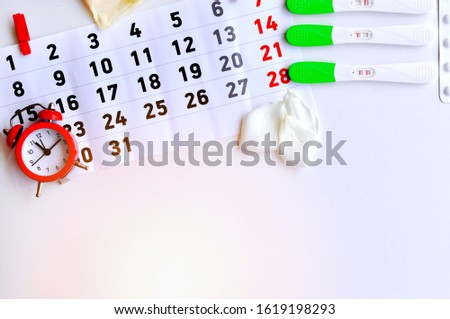 Ovulation test strip with calendar  red clock,contraception pills and menstrual pad.The tests show three different results-Positive result, It is a time for baby.Sterile days.The test is not well done