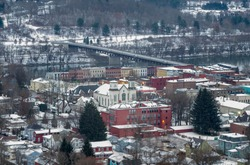 Owego is a small village in New York State, located along the Susquehanna River, photographed from the top of a hill during a winter morning with fresh snow on rooftops .