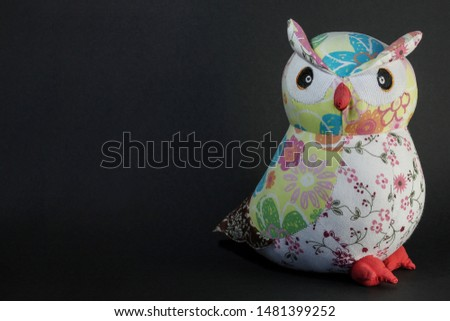 Owl toy on a black background. Wise owl in the night with place for text. Picture for wallpaper and design