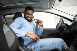 Own Car. African American Man Putting On Seat Belt Sitting In Auto In Dealership Store. Selective Focus