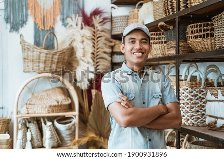 Owner a craft business with crossed hands while in a craft shop with handmade crafts on the shelf background