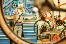 Owner bike mechanic preparing racing bicycles in workshop - Young trendy man checking new carbon fiber superbikes indoor - Professional maintenance concept -  Focus on guy - Warm filter