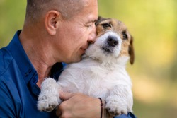 Owner hugs his pet. Man with his dog playing in the park.