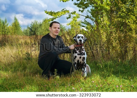 owner man sitting outdoors with a black and white spotted dalmatian dog photo