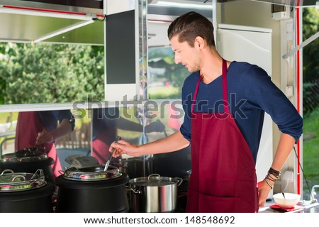 Owner of a soup kitchen or a field kitchen stirs with a ladle in the soup