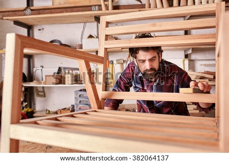 Owner of an independent furniture design and manufacturing business, working on a wooden chair frame that he has made in his woodwork studio, carefully sanding it smooth