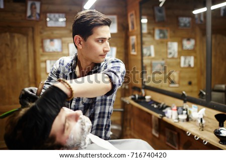 Owner of barbershop serving one of his clients in front of mirror