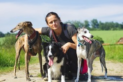 Owner on a walk with her dogs. Portarit of woman withe her dog pack in nature. Animal trainer