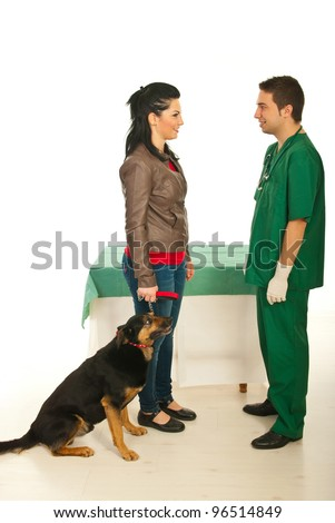 Owner woman with her dog having conversation with vet male doctor in his office