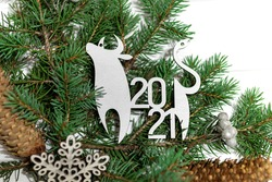 Ox and snowflake ornaments, pine braches and cones on white wooden background. New Year symbol, wallpaper