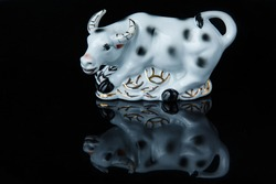 Ox as a symbol of Chinese New Year. Old white porcelain bull statuette with reflection on black background. 2021 year is a year of white metal ox