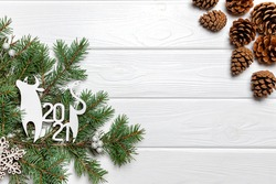 Ox ornament, snowflake, pine braches and cones on white wooden background. New Year symbol, copy space