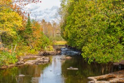 Oxtongue River Park in Dwight Ontario Canada in the Autumn season featuring gorgeous forest with vibrant fall colors , river rapids on a beautiful sunny day with blue sky