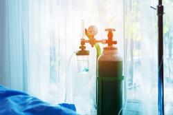 Oxygen tank beside patient bed in hospital.