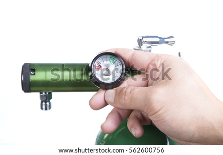 Oxygen tank with a human hand. Oxygen tank who needs refill and someone is checking the reserve. A green oxygen cylinder, a man's hand checking the oxygen reserve #562600756