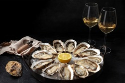 Oyster dozen with white wine and lemon, on a black background with copy space