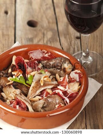 Oyster mushrooms, serrano ham and pine nuts tapas.  Setas con jamon y pinones with rioja red wine