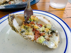 Oysters Rockefeller on a white plate with blue accents. A small fork is scooping the oyster meat out of the half shell.