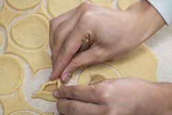 ozenei haman, Triangular pastry made of crispy dough, stuffed with poppy, halva or chocolate. For the Jewish holiday of Purim. Hands in the middle of preparation, triangles and dough circles in which
