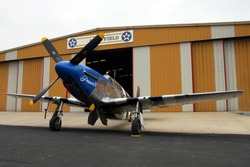 P-51B Mustang in front of airport hanger