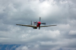 P-51 Mustang fighter aircraft against clouds