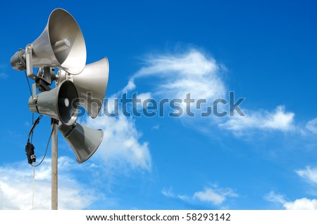 PA / Public Address system speakers, against a bright blue sky, with space for your text / editorial overlay