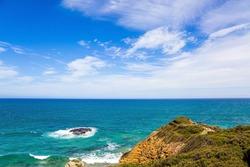 Pacific coast and sandy beach. Coastal rocks in the foam of the ocean surf. Fabulous journey to Australia. Southern Hemisphere.