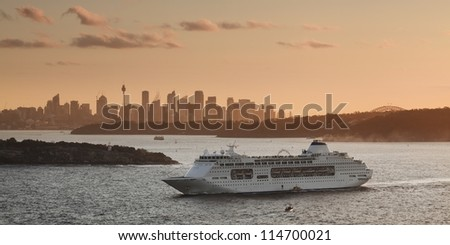 pacific cruise ship leaves sydney harbour at sunset CBD landmark in orange sun light panoramic view