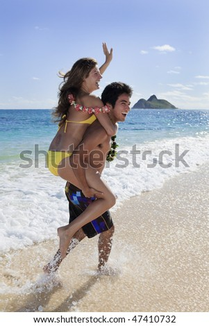 pacific island man carries a young woman on his back on a hawaii beach