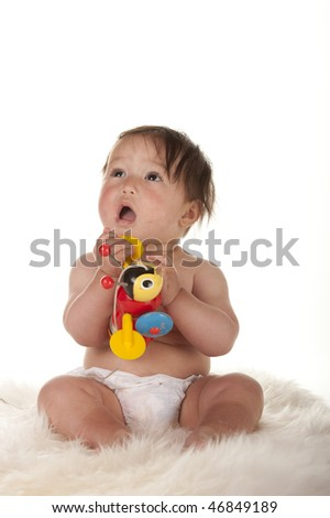 Pacific Islander baby girl sitting on sheepskin rug and holding toy and looking up with innocent face